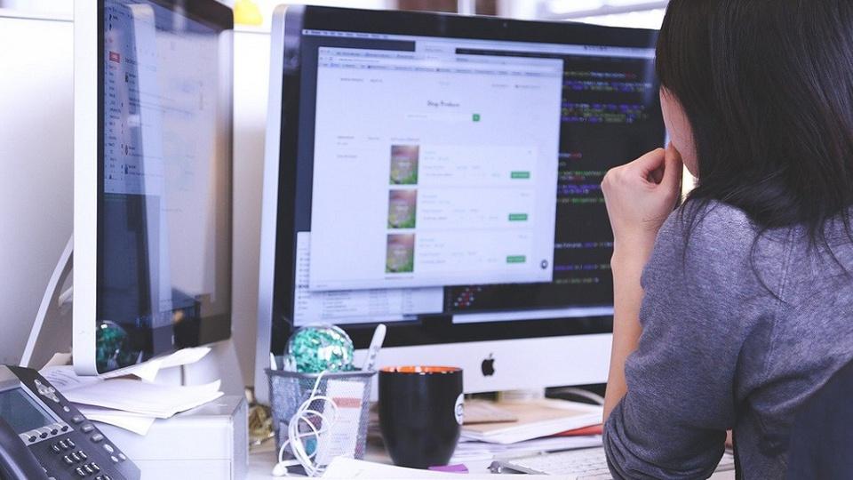 Cesar oferece vagas de emprego: mulher sentada em frente a duas telas de computador trabalhando. À sua esquerda há um telefone preto.