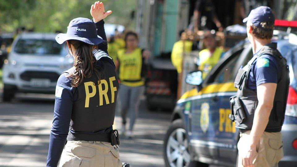 Concurso PRF: policial fazendo sinal com a mão indicando passagem e outro policial com as mãos na cintura próximo à viatura
